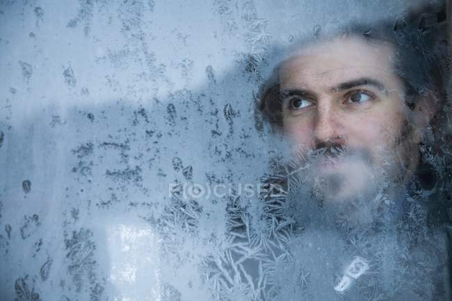 Young Man Looking Out A Frosted Window — Stock Photo