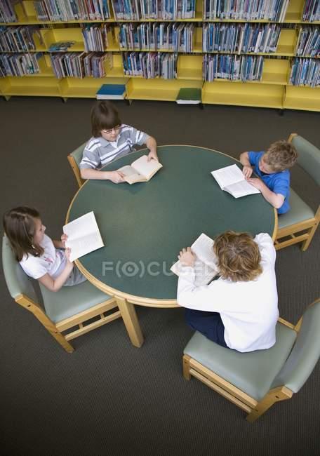 Groupe de petits enfants lisant à la bibliothèque — Photo de stock