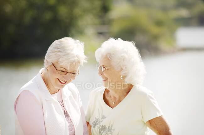 Дві старші жінки сміються надворі — стокове фото