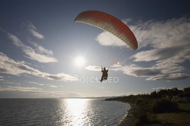 Man paragliding above water at Victoria outskirts, British Columbia, Canada — Stock Photo