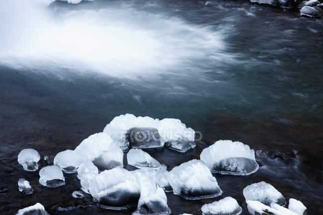 Schneebedeckte Felsen im seichten Wasser — Stockfoto