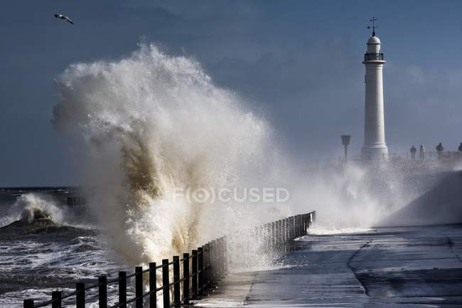 Vagues qui s'écrasent par phare — Photo de stock