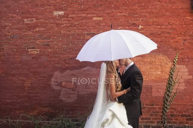 Noiva e noivo sob guarda-chuva — Fotografia de Stock