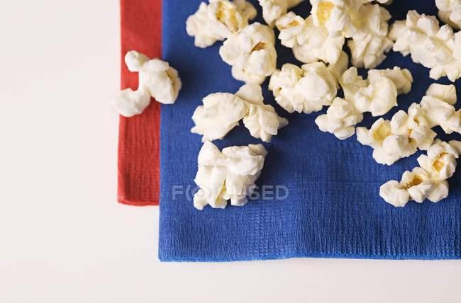 Vista superior primer plano de palomitas de maíz en servilletas azules y rojas - foto de stock