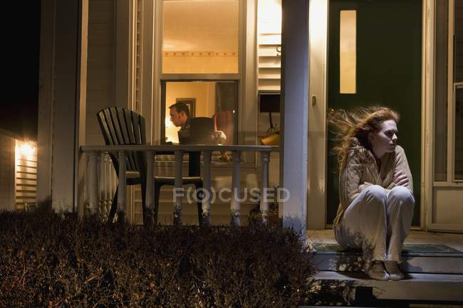 Женщина, сидящая за пределами ее дома — стоковое фото