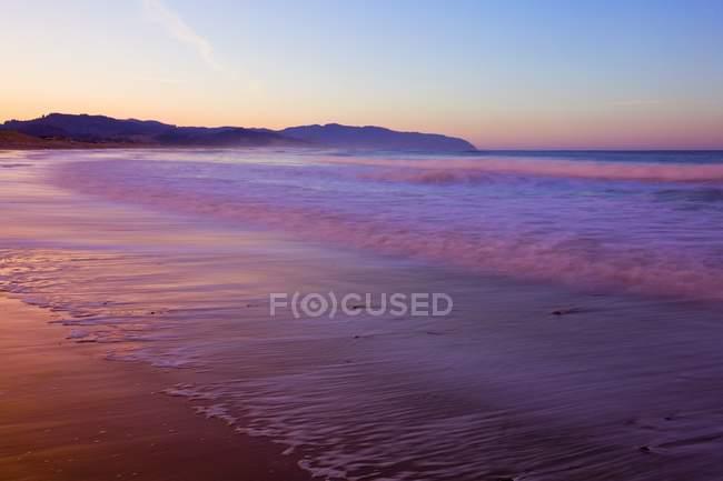 Sandy beach with wavy water — Stock Photo