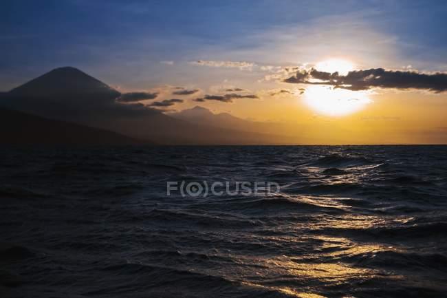 La puesta del sol sobre el agua - foto de stock