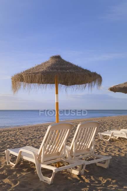 Guarda-sóis e camas de praia — Fotografia de Stock