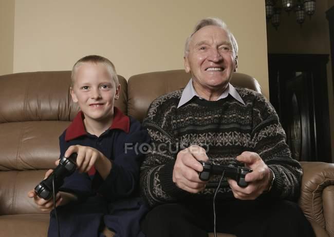 Дедушка и внук играют в игру — стоковое фото