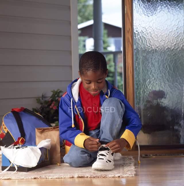 Афроамериканский мальчик привязывает новую обувь — стоковое фото
