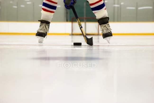 Recortar imagen de jugador de Hockey con su palo y Puck en el hielo - foto de stock