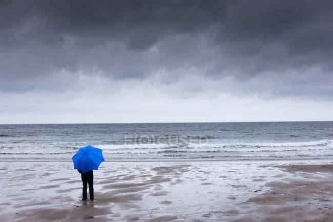 Особа, що займає синій парасолька, стоячи на пляжі з темним небом накладні витрати; Нортумберленд, Англія — стокове фото