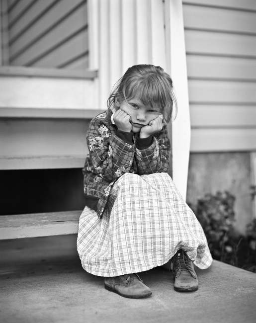 Monochrome Portrait Of Girl Sitting On Porch And Looking At Camera — Stock Photo