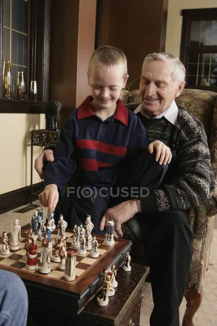 Кавказький дитину гра шахи з Дідом — стокове фото