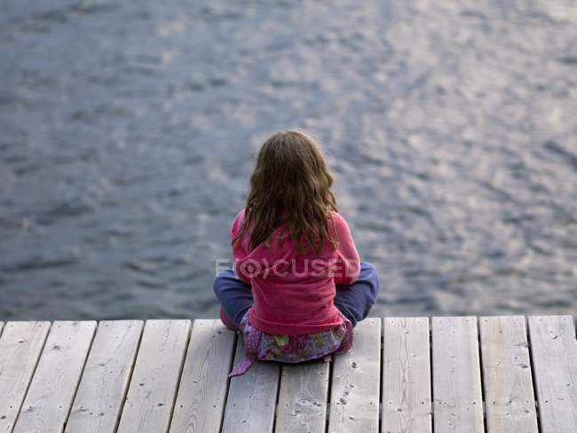 Rear view of girl sitting on dock — Stock Photo