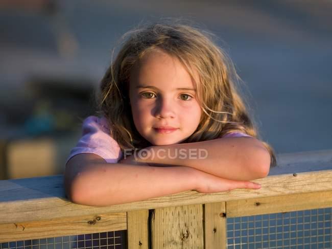 Портрет белой девушки, стоящей у ограды — стоковое фото