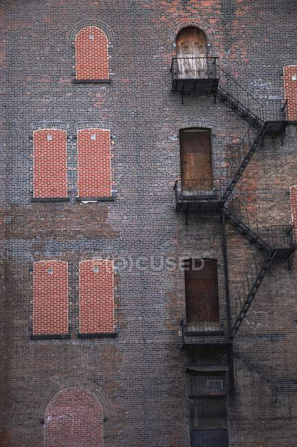 A Fire Escape Going Up The Side Of A Brick Building — Stock Photo