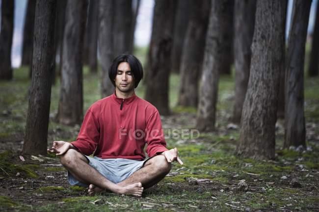 Молодой человек размышляет и практикует йогу в лесу — стоковое фото