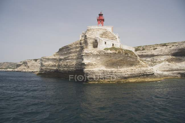 Rocky Shoreline with lighthouse — Stock Photo