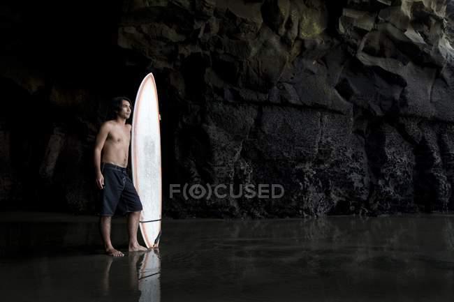 Surfista dentro de uma caverna em Muriwai Nova Zelândia — Fotografia de Stock