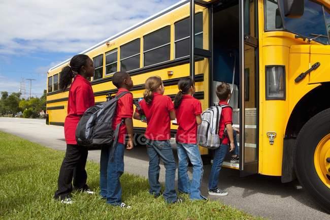 Студентів вишикувалися потрапити на шкільний автобус — стокове фото