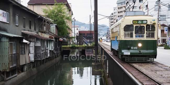 Поезд едет рядом с жильем — стоковое фото