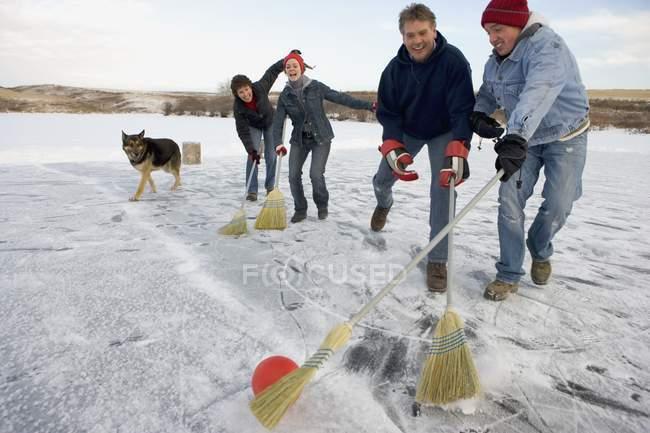 Felice famiglia caucasica al fine settimana invernale trascorrere del tempo insieme e giocare con il cane — Foto stock
