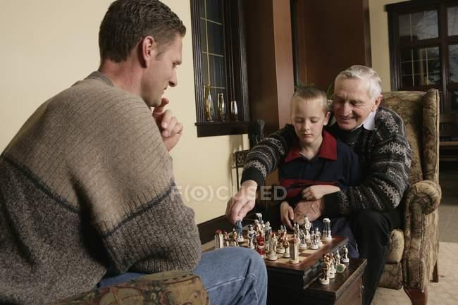Семья играет в шахматы дома — стоковое фото