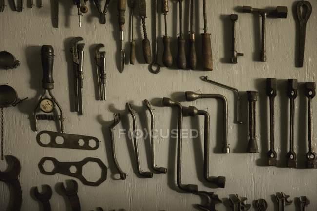 Vieux outils accroché au mur gris — Photo de stock
