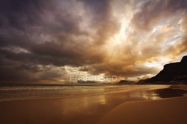 Sonnenuntergang über bewölktem Strand — Stockfoto