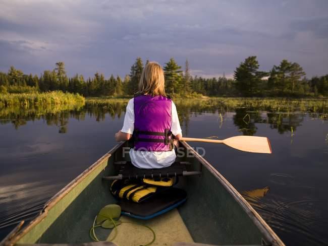 Vue arrière du canoë-kayak féminin dans le lac — Photo de stock