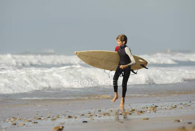 Boy Running With Surfboard Down The Beach — Stock Photo