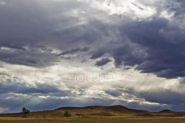 Luce del sole attraverso le nubi scure — Foto stock