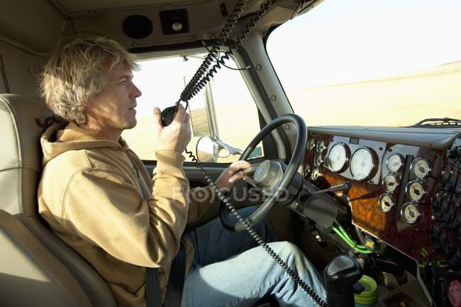 Male driver using radio in truck — Stock Photo