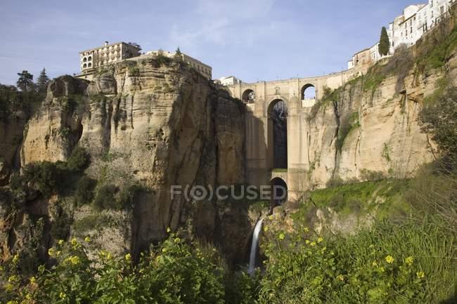 Ponte com uma cachoeira e penhascos de rocha — Fotografia de Stock