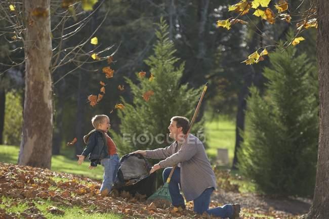 Padre e figlio insaccamento foglie insieme a parco — Foto stock