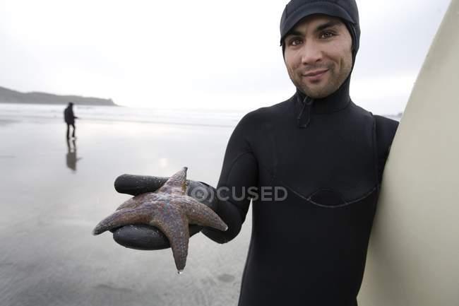 Surfer Holding Starfish in mano in spiaggia — Foto stock