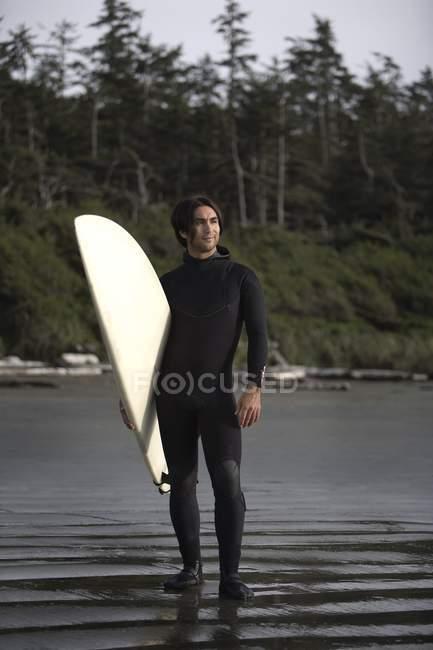 Surfeur debout sur la plage, Cox Bay près de Tofino, Colombie-Britannique, Canada — Photo de stock