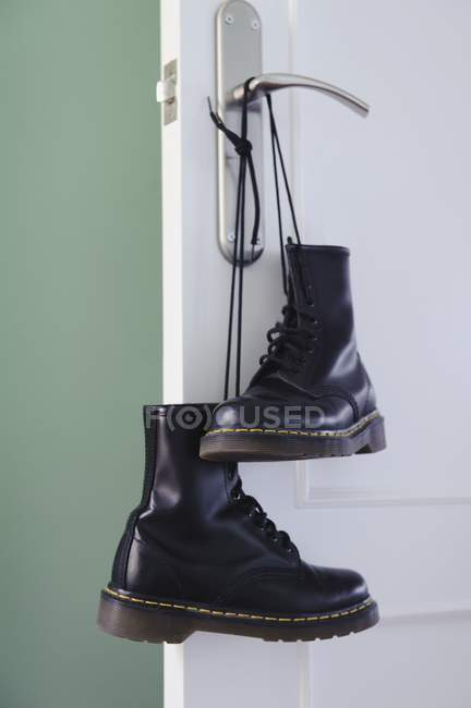 Pair of black boots tied together by laces and hanging on doorknob — Stock Photo