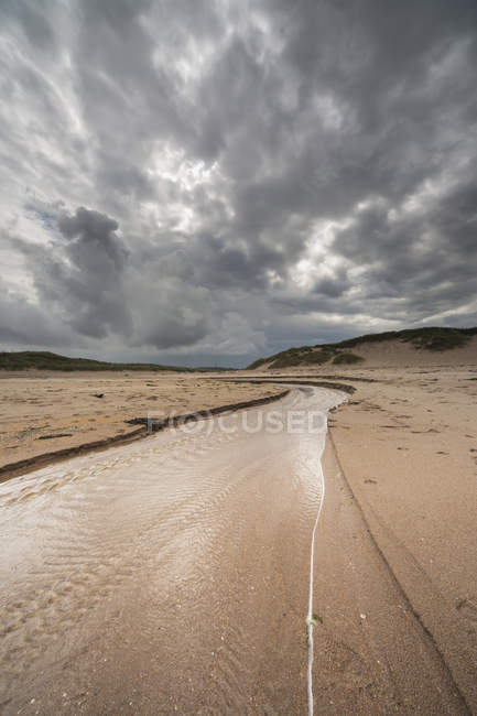Shallow water running over tire tracks in barren landscape. northumberland, england — Stock Photo