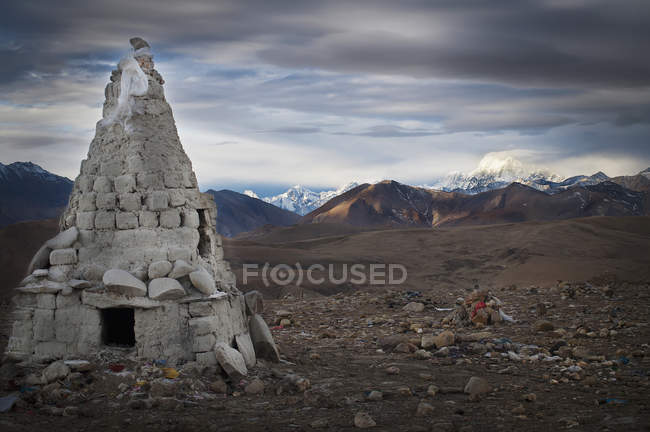 Stone conical structure on barren landscape — Stock Photo