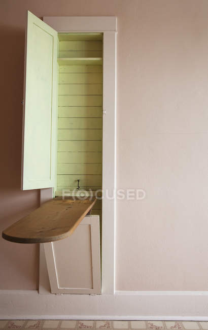 Wooden ironing board coming out of the wall — Stock Photo