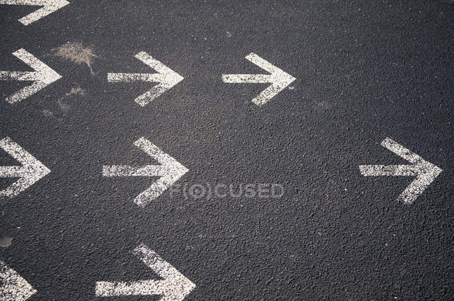 Окрашенные белые стрелки на асфальт в правильном направлении — стоковое фото