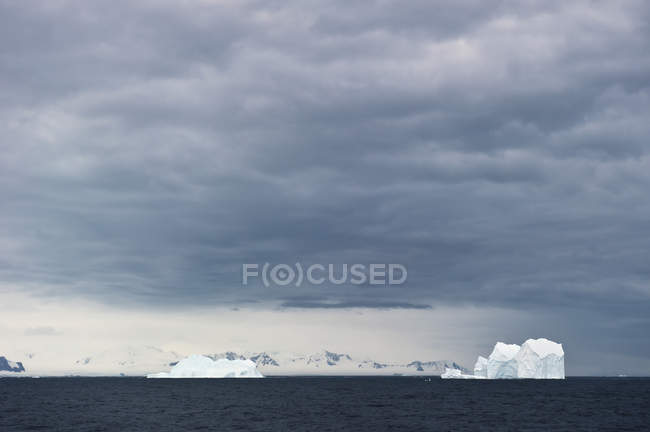 Eisberge unter bewölktem Himmel — Stockfoto