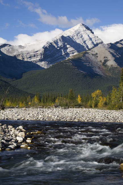 Rushing river with rocky banks and mountain range — Stock Photo