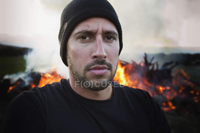 A man standing with a fire burning behind him;Dunsborough west australia australia — Stock Photo