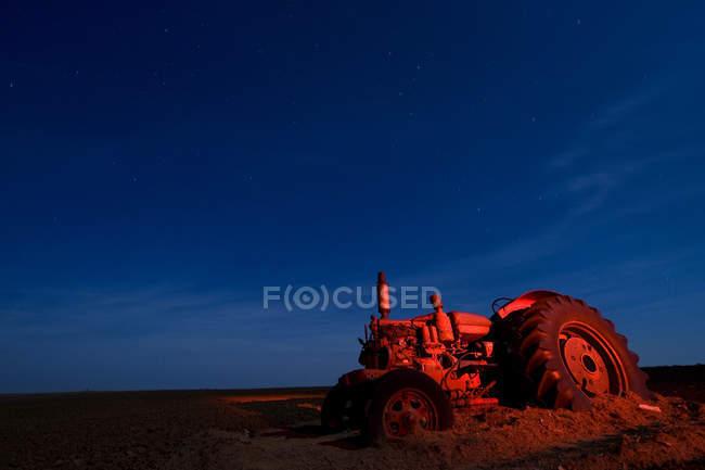 Vecchio trattore in sporcizia illuminato con luce rossa. Childress, Texas, Stati Uniti — Foto stock