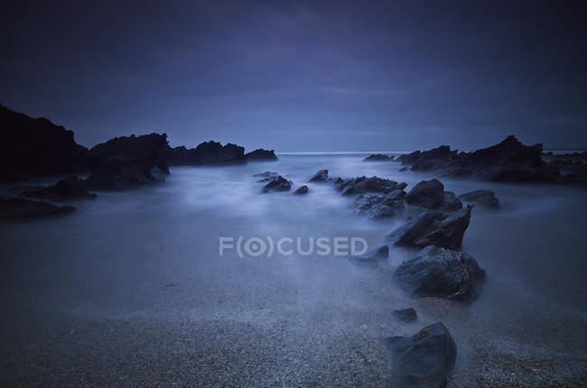 Long exposure of rocks on the beach — Stock Photo