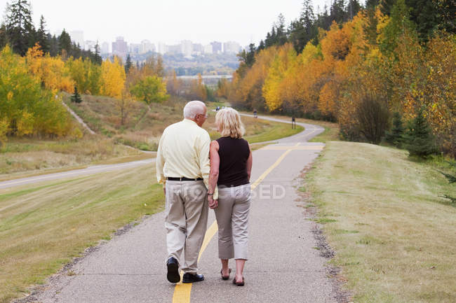 Mature married couple walking together in park during fall season;Edmonton alberta canada — Stock Photo
