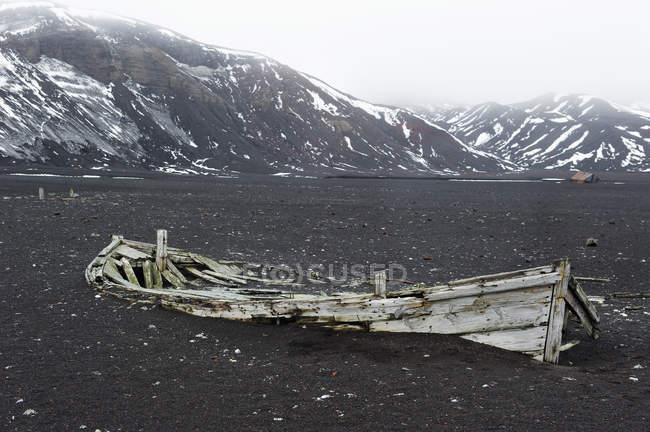 Broken abandoned wooden boat on shore — Stock Photo